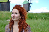 Beautiful young redhead woman looking away and thinking on the background of the mills — Stock Photo