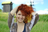 Beautiful young redhead woman smiling and holding her hands in her hair on the background of the mills — Stock Photo