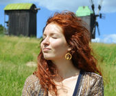 Beautiful young redhead woman smiling with hear eyes closed on the background of the mills — Stock Photo