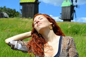 Beautiful young redhead woman smiling and holding her hands in her hair with hear eyes closed on the background of the mills — Stock Photo