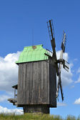Old wooden windmill in green field over bright blue sky and clouds — Stock Photo