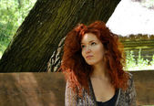 Beautiful young redhead woman looking away and thinking — Stock Photo