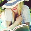 Young beautiful blond woman in summer hat with long hair smiling and reading — Stock Photo #49021387