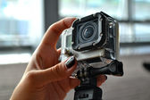 Hand holding small camera in waterproof covering — Stock Photo
