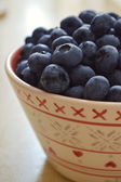 Healthy and delicious blueberries in a bowl on a wooden table — Stock Photo