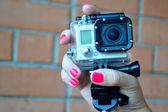 Hand with bright pink nails holding small camera in waterproof covering — Stock Photo
