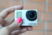 Hand holding small GoPro hero3 camera often used in extreme action video photography. — Stock Photo