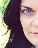 Young and beautiful brunette woman with bright green eye looking mysteriously — Stock fotografie