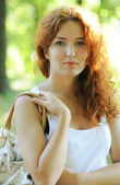 Beautiful young redhead woman smiling calmly and holding her bag — Photo