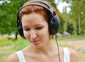 Beautiful redheaded woman in big headphones listening to the music with happy smile — Photo