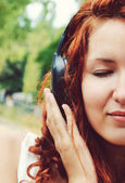Beautiful redheaded woman in big headphones listening to the music with her eyes closed — Stok fotoğraf