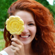 Beautiful young redhead woman smiling happily with a big flower shaped yellow lollipop — Stock Photo #51415475