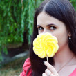 Beautiful young brunette woman with a big flower shaped yellow lollipop — Stock Photo #51415503