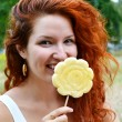 Beautiful young redhead woman smiling happily with a big flower shaped yellow lollipop — Stock Photo #51415515