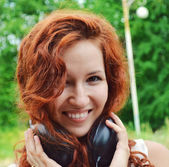 Beautiful young redhead woman smiling happily with big headphones on her neck — Photo