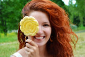 Beautiful young redhead woman smiling happily with a big flower shaped yellow lollipop — Photo