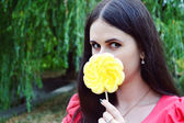 Beautiful young brunette woman with a big flower shaped yellow lollipop — Photo