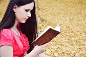 Beautiful brunette woman with long hair reading against autumn nature — Photo