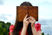 Shy brunette woman hiding behind a notebook — Photo