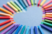 Colorful chalk pastels in shape of heart — Stock Photo