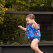 Stock Photo: Infant girl running by pool 1