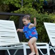 Stock Photo: Infant girl running by pool 2
