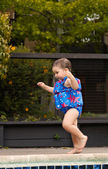 Infant girl running by the pool 1 — Stock Photo