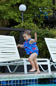 Infant girl running by the pool 2 — Stock Photo