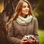 Girl with retro camera in the park near tree — Stock Photo