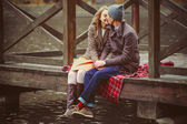 Lovers woman and man sitting near the lake — Stock Photo