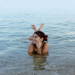 Beautiful girl floating in the Dead Sea — Stockfoto