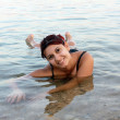 Beautiful girl floating on the Dead Sea — Stockfoto