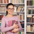 Cheerful young female student holding books  — Stock Photo