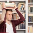 Cheerful young man holding a book stack on his head  — Stock Photo