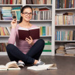 Cheerful young female student holding book — Stock Photo