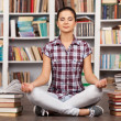 Beautiful young woman meditating while sitting at the library — Foto de Stock