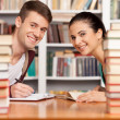 Young man and woman sitting at the library desk — ストック写真