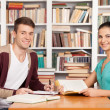 Cheerful young man and woman sitting at the library desk — Stock Photo