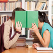Stock Photo: Young man and woman hiding their faces behind a book
