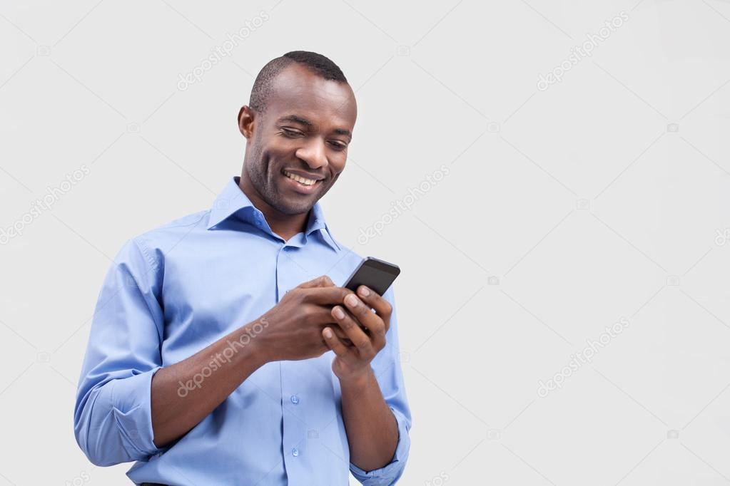 Black Man on Phone Cheerful Black Man Typing