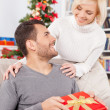 Man holding a gift box while her girlfriend standing behind him — Stock Photo
