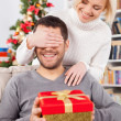 Man holding a gift box while her girlfriend covering his eyes with hands — Stok fotoğraf