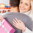 Woman hugging her boyfriend and holding a gift box — Foto Stock