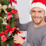 Man decorating a Christmas tree — Stock Photo