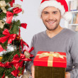 Man holding a gift box near the Christmas tree — Stock Photo #37047111
