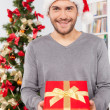 Man holding a gift box near the Christmas tree — Stock Photo #37047139