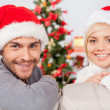 Couple in Santa hats sitting on the couch — Stock Photo