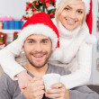 Man sitting with girlfriend Christmas hats and holding a cup — Stock Photo