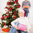 Woman sitting near the tree and holding a gift box — Stock Photo