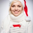 Woman in Santa hat holding a red cup and smiling — Stock Photo